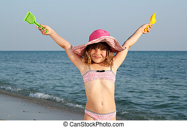 happy little girl with hands up on beach