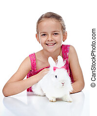 Happy little girl with her cute rabbit
