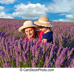 Happy little girl with her mother are in a lavender field