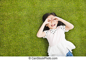happy Little girl with looking gesture on the grass