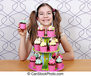 happy little girl with muffins cakes
