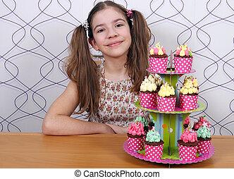 Happy little girl with muffins dessert