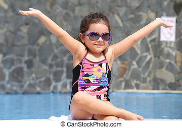 Happy little girl with open arms outside the pool