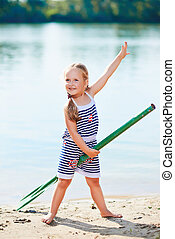 happy little girl with paddle at beach