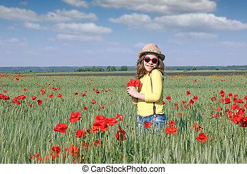 happy little girl with poppy flower spring season