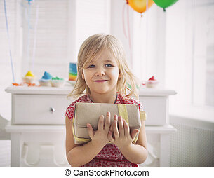 Happy little girl with present celebrating her birthday