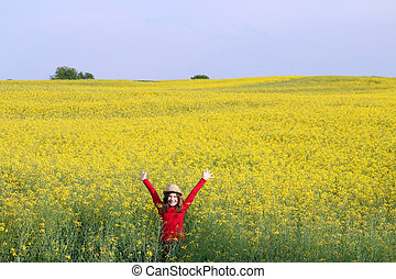 happy little girl with straw hat on field summer season