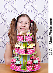 Happy little girl with sweet muffins cake