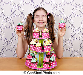 Happy little girl with sweet muffins