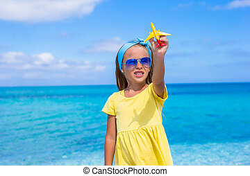 Happy little girl with toy airplane in hands on white beach