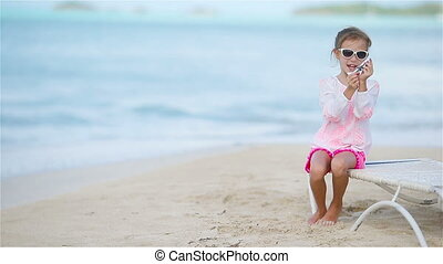 Happy little girl with toy airplane in hands on white beach...