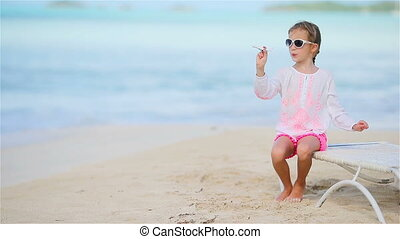Happy little girl with toy airplane in hands on white sandy beach. Kid play with toy on the beach