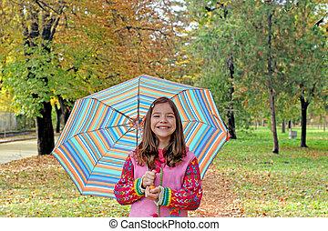 happy little girl with umbrella autumn season
