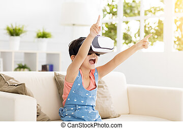 happy little girl with virtual reality headset sitting on sofa
