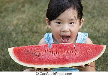 Happy little girl with watermelon in a garden