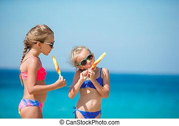 Happy little girls eating ice-cream on the beach.