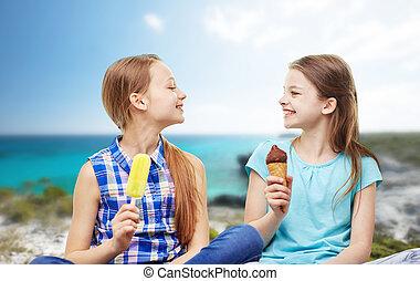 happy little girls eating ice-cream over beach