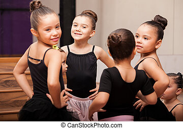Beautiful little girls wearing tights and skirts having fun in a ballet class and smiling