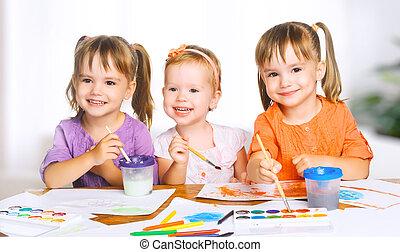 happy little girls in kindergarten draw paints
