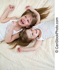 happy little girls lying on back top view
