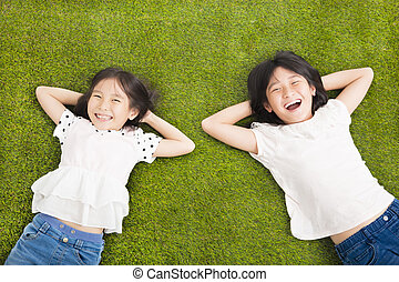 happy Little  girls resting on the grass