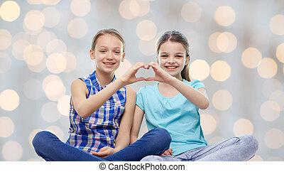 happy little girls showing heart shape hand sign - people,...
