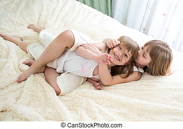 happy little girls sisters hugging and kissing on bed