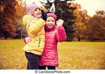 happy little girls waving hands in autumn park