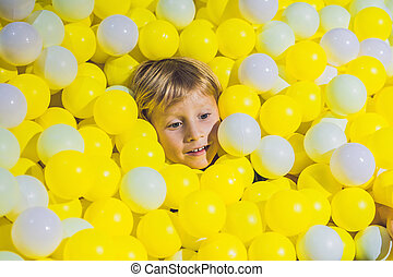 Happy little kid boy playing at colorful plastic balls...