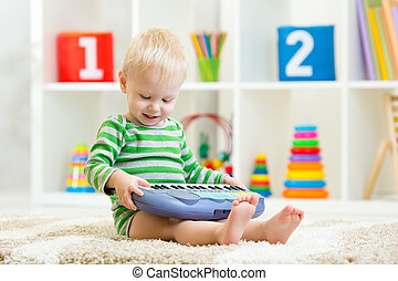 Happy little kid boy playing piano toy