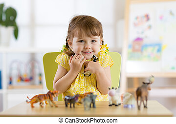 Happy little kid girl. Smiling child toddler plays animal toys at home or kindergarten