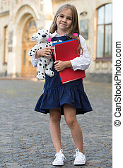 Happy little kid in school uniform hold study books and toy dog outdoors, September 1.