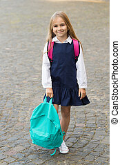 Happy little kid smile in fashion uniform holding backpack outdoors, back to school.