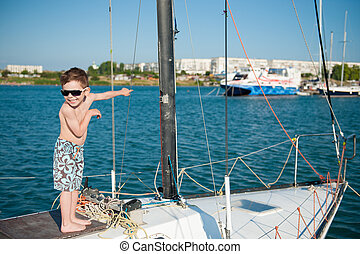 happy little kid wearing shorts and sunglasses aboard luxury yacht