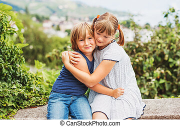 Happy little kids hugging each other, brother and sister playing together, siblings love