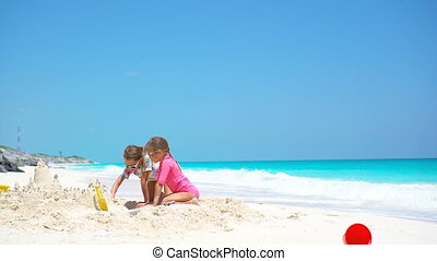Happy little kids playing with beach toys during tropical vacation