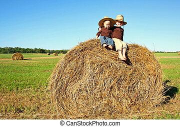 Happy Little Kids Sitting on Hay Bale at Farm