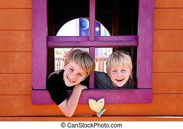 Two happy little kids, brothers, are smiling at the park as they peek out the window of a clubhouse fort.