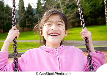 Happy little nine year old part Asian girl smiling on a swing at the park