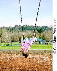 Happy little nine year old part Asian girl swinging upside down