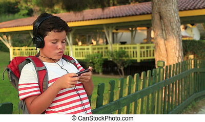 Happy little schoolboy listening to music and gaming on the smartphone