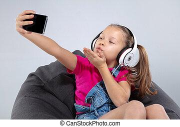 happy little schoolgirl using smartphone and listening music with headphones