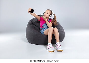 happy little schoolgirl using smartphone and listening music with headphones
