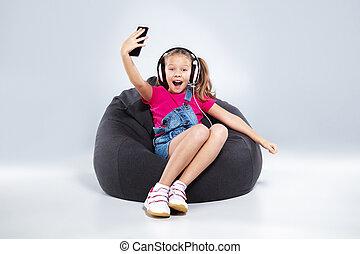 happy little schoolgirl using smartphone with headphones