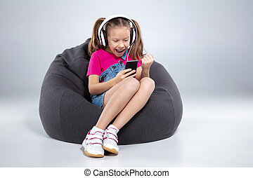 happy little schoolgirl using smartphone with headphones