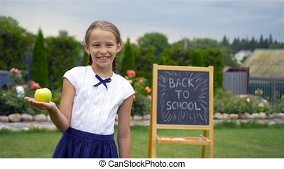 Happy little schoolgirl with a chalkboard outdoor - Happy...