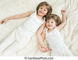happy little sisters lying on back top view