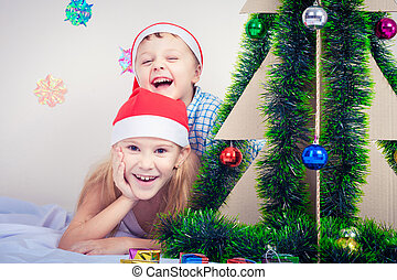 Happy little smiling boy and girl with christmas hat.