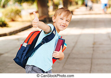 Happy little student with schoolbag. Cute boy with notebooks and backpack are ready to study.