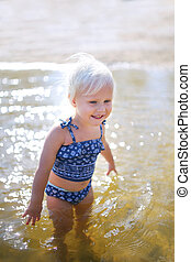 Happy Little Toddler Child Swimming in Lake on Summer Day